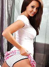 Busty brunette gets flirty in her bedroom as she poses in her tight top and miniskirt and flashes her sexy curves.